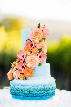 Ombre blue wedding cake with coral flowers