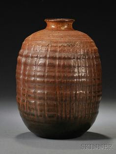 Mid-20th Century Glazed Stoneware Studio Vase, flared rim on ovoid body in grainy brown glaze with incised vertical lines, indistinguishable signature on base, ht. 9 in.
