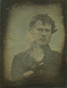 "One of the earliest known photographs of a human. Robert Cornelius's self-portrait. The back reads, ""The first light picture ever taken."" 1839. Robert Cornelius (1809-1893) standing outside his family's lamp-making shop in Philadelphia. Cornelius was an American of Dutch descent whose knowledge of metallurgical chemistry was to help in perfecting the process of silver-plating, then employed in the production of daguerreotypes."