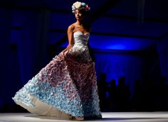 A model wearing a dress with flowers by Whitney Rorah Design during Omaha Fashion Week's first day on Monday, August 18, 2014. By: CHRIS MACHIAN/THE WORLD-HERALD