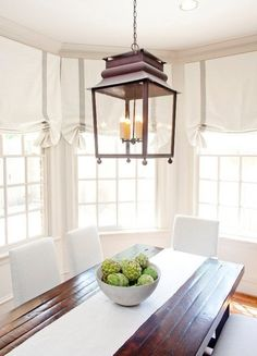 Simple, neutral, with exquisite elements. Gorgeous table, lighting, curtains, windows.