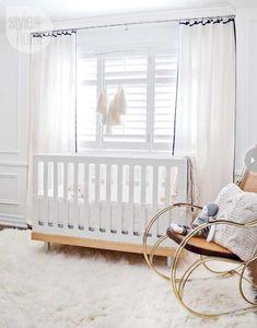 Modern crib, plush rug and vintage rocking chair. All white nursery