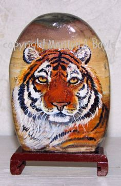 I painted this tiger head on a rock that was attached to a wood stand.