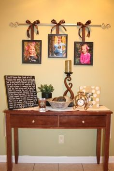 pictures on curtain rod. Did something similar over the mantel and I LOVE it.