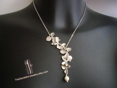 Asymmetrical flowers cascade necklace in white gold.