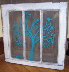 Shabby white vintage 3 pane window with little teal bird singing in a swirly tree