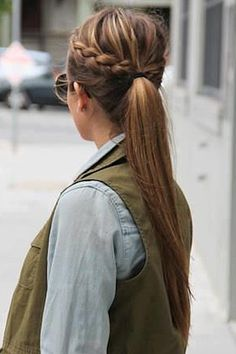 Try a braided ponytail by Dutch (inside-out) braiding on both sides at the center part and finishing at the center of the head. Gather both braids and the rest of the hair into a ponytail.