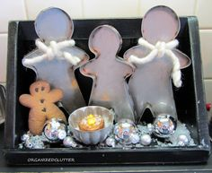 gingerbread pans, a gingerbread look cookie, a Jello mold with a grubby flameless candle, silver ornaments in a couple sizes and some faux snow. The gingerbread pan men have thick Alpine looking yarn tied around their necks.