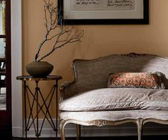 The slight orange hue of the wall is encouraged by a lone throw pillow in this vintage-look entry. | Hotel St. Francis Fawn 3001-9C, @valsparpaint Reserve
