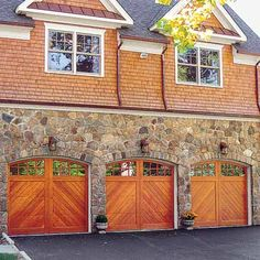 Arched wood garage doors with divided-light windows and herringbone panels give this home the look of a Victorian-era stable. Shown: Northwest Door Heritage Classic model C008C sectional insulated western red cedar, starting at $3,000; nwdusa.com