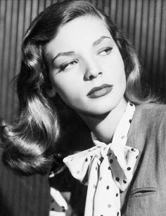 Lauren Bacall Could Teach You a Thing or Two About Style. She chose a bold tie-neck blouse for a 1945 publicity photo. Also we love those lips.  Photo: Corbis