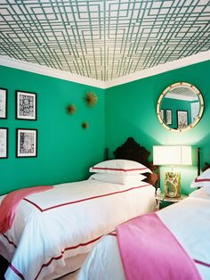 Bedding with trim, bold wallpaper on the ceiling and a vibrant hue on the walls balanced by whites