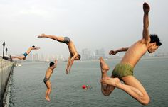 Chinese men jump into the Han River during a hot summer day in Wuhan in central China's Hubei province Friday, July 2, 2010.