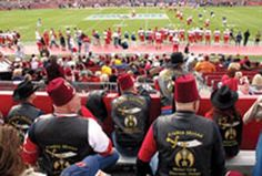 Shriners in their red fezzes watch the 84th annual East-West Shrine Game, which raises funds for Shriners Hospitals for Children