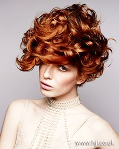 Long red hair was prepped with mousse and roughly blow-dried to add volume and texture. Once dry, hair was tonged in small sections to create tight curls. Hair was then smoothed throughout with serum to create glossy ringlets and piled up on top of the head in a loose updo. #redheads