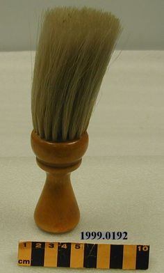 This brush, which was used to remove cut hair from a customer's neck and facial area, is part of a collection of barbering equipment that was donated to the museum in 1999.