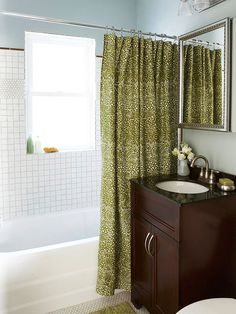 Pretty shower curtain and cool tile in the shower and on the floor.
