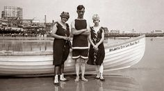 """Circa 1920, beachgoers stand in front of a boat in <a href=""""http://www.travelchannel.com/destinations/atlantic-city/photos/historic-atlantic-city  """">Atlantic City, NJ</a>."""