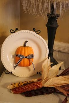 Dollar Store pumpkin cut in half, wrapped in ribbon, and glued to a plate.