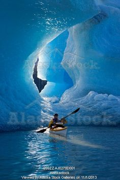 Photo of Sea kayaker on Mendenhall Lake with big blue iceberg in the background, Southeast Alaska, Summer