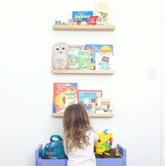 Ikea ribba picture ledges for displaying children's books and small toys in the playroom