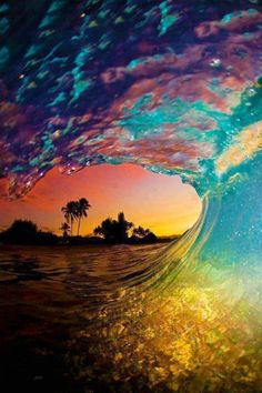 the splashes of different colours in the wave make it seem magical, and with the island in the background through the tube of the wave adds to that.