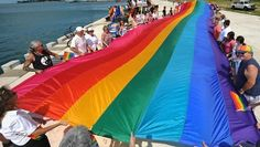 PHOTO: Participants at a National Coming Out Day rally unfurl a large rainbow flag, Oct. 11, 2011, in Key West, Fla.