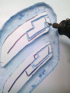 Using a Dremmel tool to cut, sand and add detail to blue/pink insulation foam.