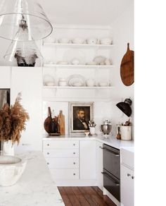 white walls; white cabinets; white counters; open shelves