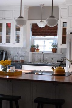 one of my fav kitchens:  cabinet color: Benjamin Moore's White Dove  wall color: Rockport Grey from Benjamin Moore (other top runner up: Benjamin Moore's Sandyhook Gray)  The pendants are from Rejuvenation   curtains from target
