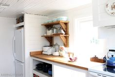 Farmhouse kitchen makeover - white painted cabinets, reclaimed and Ikea butcher block countertops, cast iron drainboard sink, open shelving