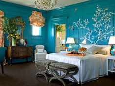 Bright blue bedroom with wall print tree