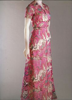 """1938 """"Circus Collection"""" dinner dress by Elsa Schiaparelli, printed silk chiffon. This short-sleeved ankle-length dinner dress with a flaring skirt is made of sheer pink silk chiffon printed with circus motifs, via Philadelphia Museum of Art."""