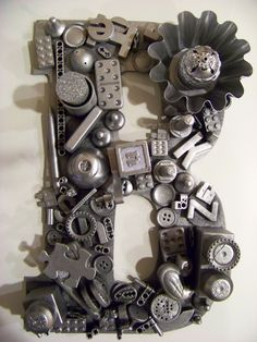 recycled toys on wood letter, spray with black spray paint and follow with silver