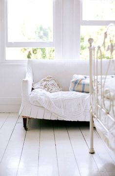 white floor boards and sofa with dark legs.