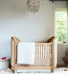 Glam damask wallpaper in this neutral baby girl nursery.  #white #nursery #genderneutral #modernglam