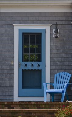 Cape Cod Cottage with blue screen door that has a sailboat design.