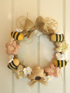 Guirlanda com base de palha, enfeitada com flores e abelhas de tecido 100% algodão e pintura à mão. Perfeita para quartinhos infantis ou para receber os amigos na porta de casa! R$ 55,00
