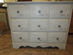 old brown dresser, painted light gray with dark gray numbers, new knobs, distressed, antique and clear waxed.  Picture does not do it justice!