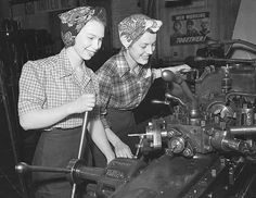 Two women operate a machine in a factory during World War II. Captured by a Minneapolis newspaper photographer on March 3, 1943.