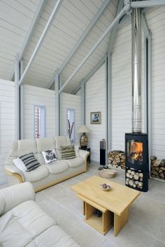 Love these soft cool colors. A very different type of barn room with painted timber and woodburner. By Roderick James Architects