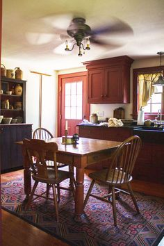 kitchen red cabinets and trim black marble counters farmhouse sink wood floors eating table Micah Rich Sneak Peak DesignSponge