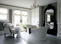 Elegant ensuite with gray damask wallpaper, white silk roman shades with gray ribbon trim, French doors, glossy black Bergere chair upholstered in white linen fabric, marble tiles with mosaic marble inset tiles, Freestanding oval bathtub, white linen cabinets and glossy black rococo floor mirror.