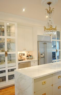 Stunning white and gold kitchen with campaign style hardware. Love that island! by Meredith Heron Design