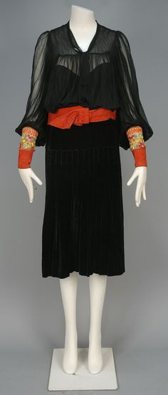 WORTH NET and VELVET DRESS with BEADED and SUEDE DETAILS, 1920s. Black net bodice ruched below yoke having full sleeve gathered into a polychrome beaded band with sequins above red suede cuff, attached suede belt, silk velvet skirt having pleated center panel and interior hanging weights, silk lining. London label.