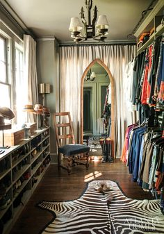 Nice grey walls and shooe shelves under windows in this large walk in closet.  The curtain at the end behind the mirror probably hides STUFF!