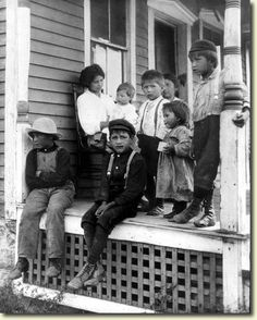 A young Indian woman and seven children: babies, toddlers, and older children, gathered on the porch of a wooden house; Onondaga reservation, (1910).