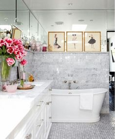 Bathroom. Marble with mirror above. White cabinetry. Free standing tub. Wall-mount tub faucet. Picture ledge.