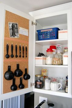 12 Easy Kitchen Organization Tips | Cork board inside of kitchen cabinets to pin recipes and hooks for measuring spoons.