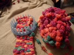 Pom Pom scarf on a loom. They can be made on a loom but you have to use a small loom or it will have holes between the  Pom poms.